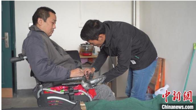 大学生带瘫痪父亲上学